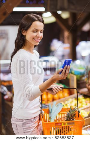 sale, shopping, consumerism and people concept - happy young woman with food basket and smartphone in market