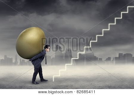 Male Worker Carry Golden Egg To The Sky