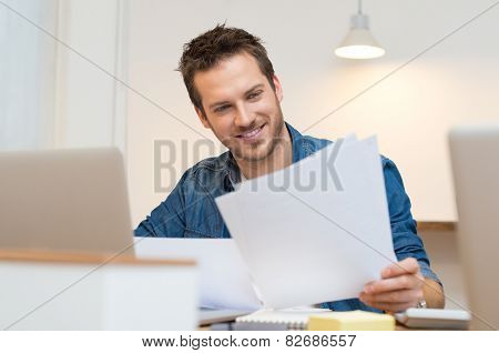 Happy young businessman reading paperwork at desk in office