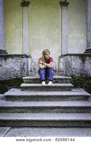 Young girl sitting on a marble staircase. Color image