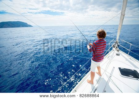 Young man fishing in the sea from sail boat