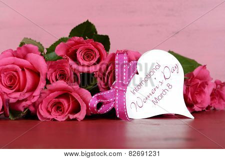 International Womens Day, March 8, Pink Roses With Gift Tag Message On Vintage Pink Wood Background.