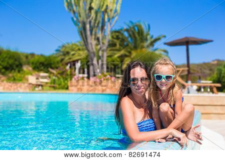 Mother and little girl relaxing in luxury quiet swimming pool