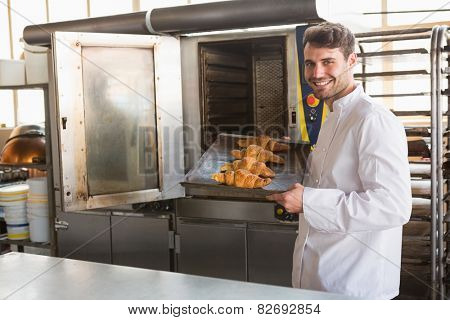 Smiling baker taking fresh croissants out of the oven in the kitchen of the bakery