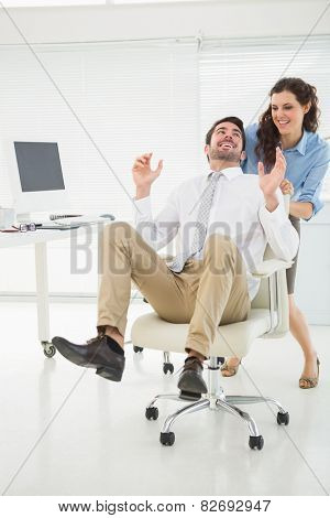 Smiling partners playing together with swivel chair in the office