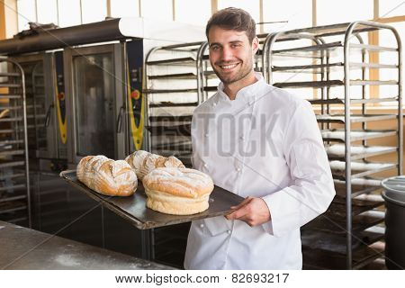 Happy baker showing tray with bread at the bakery