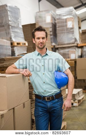 Smiling warehouse worker leaning against boxes in a large warehouse
