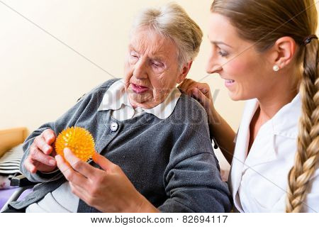 Nurse giving physical therapy with massage ball to senior woman in wheelchair