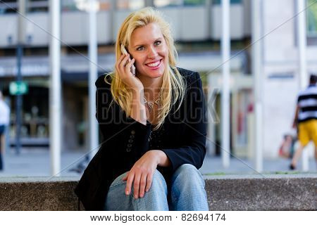 Mature woman telephoning with smartphone in city