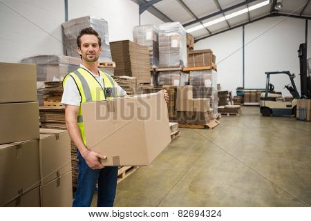 Portrait of worker carrying box in the warehouse