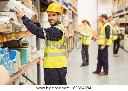 Smiling warehouse worker taking package in the shelf in a large warehouse