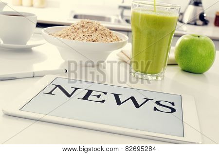 closeup of the kitchen tablet set for breakfast with a bowl with cereal, an apple and a glass with a smoothie and a tablet computer where to read the news