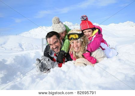 Portrait of happy family laying down in snow