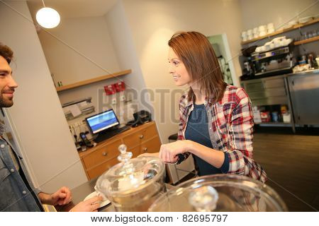 Woman in coffee shop serving customer