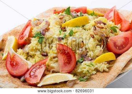 Levantine sayyadiyya, fish pilaf in saffron rice, garnished with lemon, tomato, pine-nuts and fried onion, on a bed of bread.