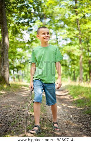 Cute Boy Walking Through The Forest