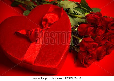 Long stem red roses and box of candy on a red background.  Valentine's day gift, symbol of love and passion