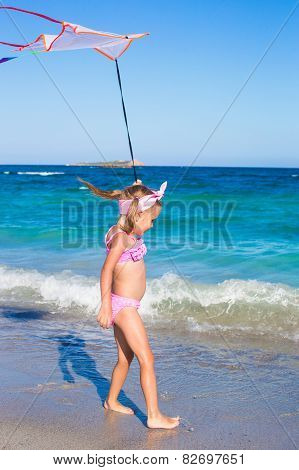 Little adorable girl playing with flying kite during tropical beach vacation