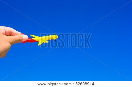 Small plane in hands on background of blue sky