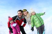 foto of family ski vacation  - Cheerful family of 4 enjoying winter vacation - JPG