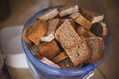 image of homeless  - cut bread in bucket for homeless people in ukraine
