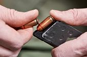 stock photo of ammo  - Soldier load ammo in the clip gun - JPG