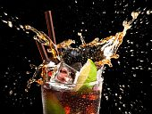 foto of ice-cubes  - Ice cube and lime splashing cola in glass cuba libre black background closeup - JPG