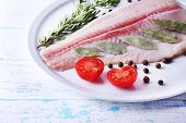 stock photo of pangasius  - Pangasius fillet with herb and sliced cherry tomatoes on plate and color wooden table background - JPG