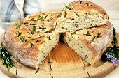 stock photo of flat-bread  - Homemade rustic Italian rosemary Focaccia bread on a wooden board - JPG