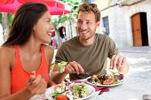 Постер, плакат: Restaurant tourists couple eating at outdoor cafe Summer travel people eating healthy food together