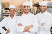 picture of team building  - Team of bakers smiling at camera in the kitchen of the bakery - JPG
