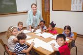 stock photo of classmates  - Teacher and pupils working at desk together at the elementary school - JPG