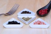 pic of peppercorns  - A Variety of peppercorns and salt on a table - JPG