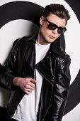 foto of jacket  - Handsome male model in leather jacket posing against target background - JPG