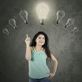 stock photo of lightbulb  - Young casual woman with curly hair standing under lightbulb while choosing one of the bright lightbulb - JPG