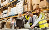 stock photo of warehouse  - Warehouse managers and worker talking in a large warehouse - JPG