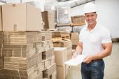 foto of warehouse  - Smiling warehouse worker with clipboard in warehouse - JPG