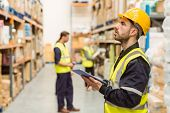 stock photo of warehouse  - Focused warehouse manager writing on clipboard in a large warehouse - JPG