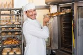 stock photo of bagel  - Happy baker taking out fresh bagels in the kitchen of the bakery - JPG