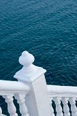 stock photo of bannister  - White balustrade with ocean blue background Mediterranean colors - JPG