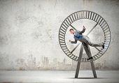 image of hamster  - Young businessman running in huge hamster wheel - JPG