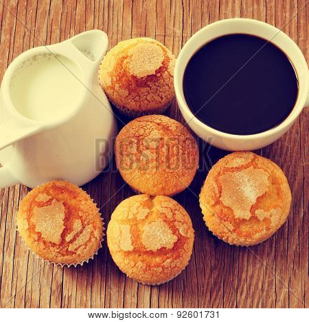 closeup of a porcelain pot with milk, a porcelain cup with coffee and a pile of muffins on a rustic wooden table