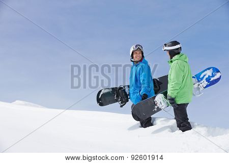 Two Men With Snowboards On Ski Holiday In Mountains