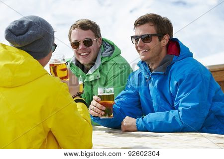 Group Of Young Men Enjoying Drink In Bar At Ski Resort