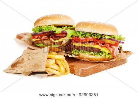 Delicious hamburger and fries on wooden background