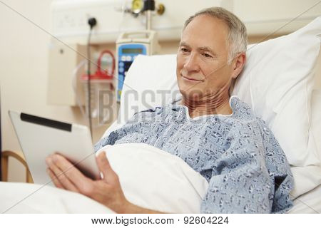 Senior Male Patient Using Digital Tablet In Hospital Bed