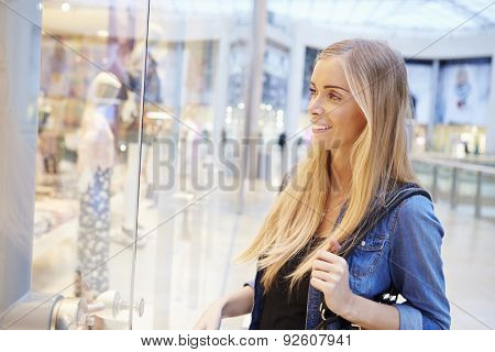 Female Shopper Looking In Store Window Inside Shopping Mall