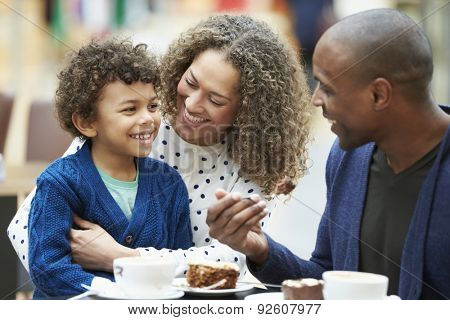 Family Enjoying Snack In Caf\x81_ Together