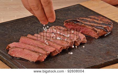 Cook seasoning grilled beef steak on hot stone.adding salt.