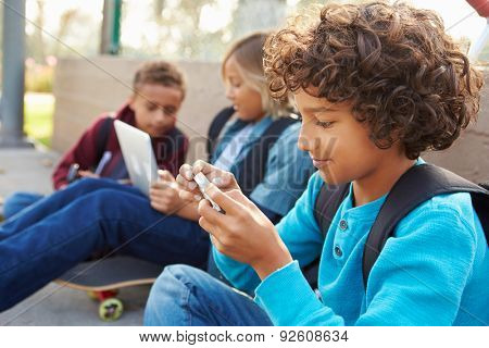 Young Boys Using Digital Tablets And Mobile Phones In Park